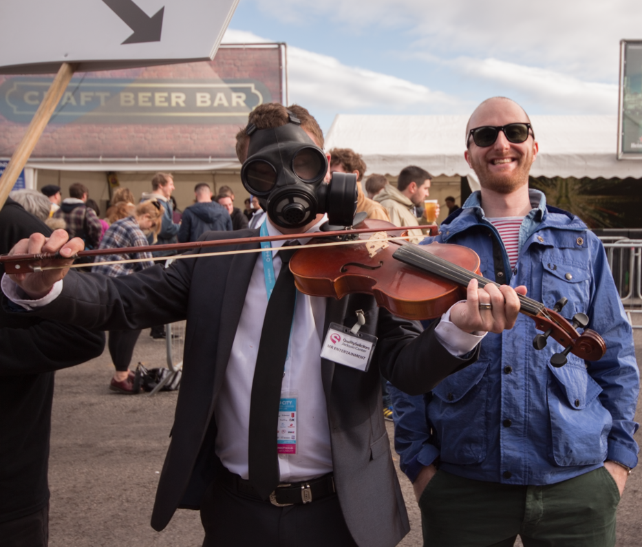 Festival Insights' Tom Lawson (right) with Man In Gas Mask With Violin (left)